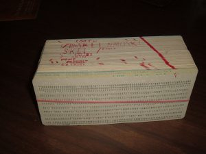 A computer program contained in a stack of punched cards, waiting to be inserted into a machine that can read them. You can see edits in red marking where the programmer has made changes from the last iteration.
