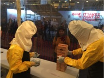 Participants at the Ebola Treatment Unit interactive exhibit at the 2015 ASTMH annual meeting attempt to play Jenga in full PPE. Image: Tropmed2015.tumblr.com