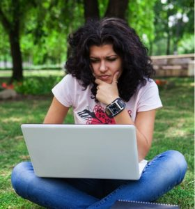 A student completes coursework outside on her laptop.